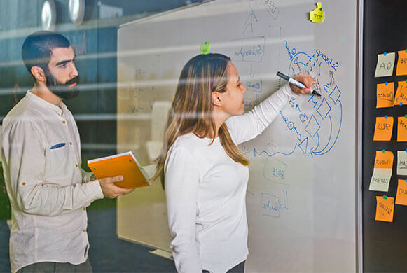 two colleagues writting on a board about planning an event
